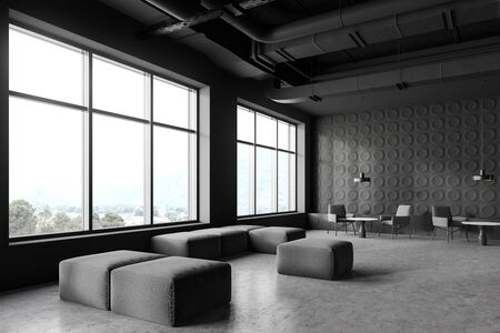 Corner of modern industrial style office lounge area with dark gray walls, concrete floor, grey armchairs near coffee tables and windows with mountain view. 3d rendering