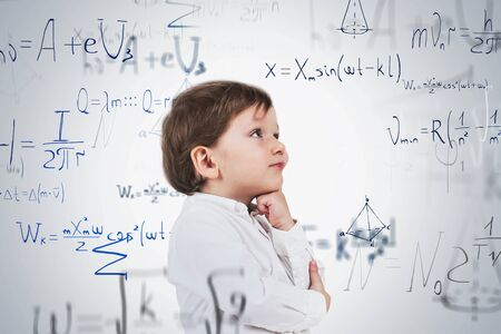 Adorable little boy in white shirt thinking hard standing near white wall with formulas written on it. Concept of education and science. Double exposure Standard-Bild - 129260051