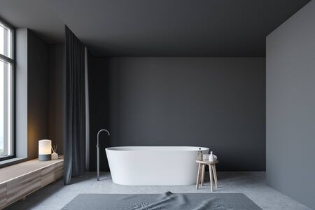 Interior of minimalistic bathroom with gray walls, concrete floor, comfortable white bathtub with carpet near it and dark gray curtains. 3d rendering Zdjęcie Seryjne