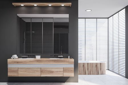 Interior of modern bathroom with gray walls, tiled floor, double sink standing on wooden countertop and comfortable wooden bathtub in background. 3d rendering Фото со стока