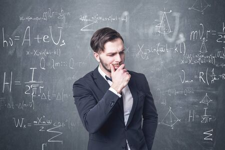 Thoughtful bearded man in dark suit standing near blackboard with formulas written on it. Concept of education and science.