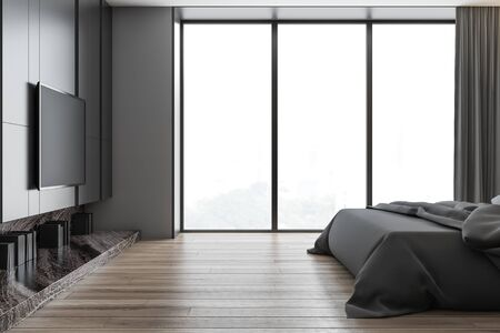 Interior of panoramic bedroom with gray walls, wooden floor, king size bed with gray blanket and modern TV set on the wall. 3d rendering