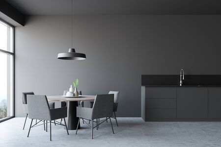 Interior of modern dining room and kitchen with gray walls, concrete floor, round table with grey chairs and dark gray countertop with built in sink. 3d rendering Фото со стока