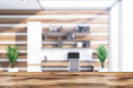 Blurred interior of office workplace with white and wooden walls, wooden computer table with shelves with folders above it and metal chair. Table for your product in foreground. 3d rendering