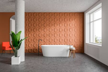 Interior of stylish bathroom with orange and white walls, concrete floor, comfortable white bathtub and bright orange armchair near column. 3d rendering Zdjęcie Seryjne