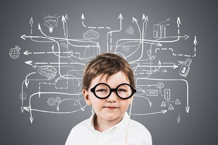 Adorable little boy in glasses standing near gray wall with business plan sketch drawn on it. Concept of future of business.