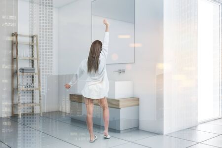 Woman in pajamas standing in modern white bathroom corner with white walls, tiled floor and comfortable double sink with large mirror. Toned image double exposure Zdjęcie Seryjne