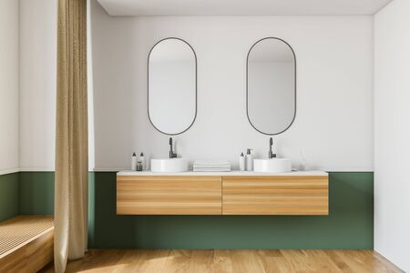 Interior of modern bathroom with white and green walls, wooden floor, double sink standing on wooden countertop and two oblong mirrors. 3d rendering Фото со стока