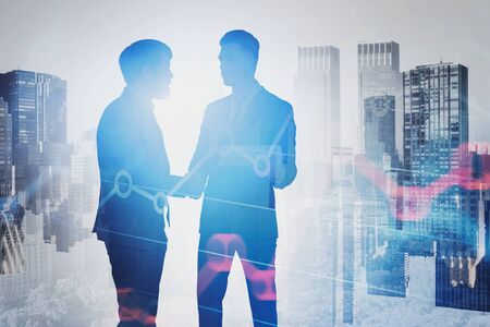 Two unrecognizable businessmen shaking hands in city with double exposure of graphs. Concept of partnership and stock market. Toned image Zdjęcie Seryjne