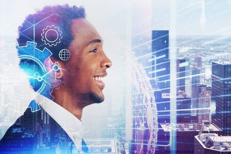 Side view of smiling young African American businessman in city with double exposure of gears and internet hologram. Concept of hi tech. Toned image