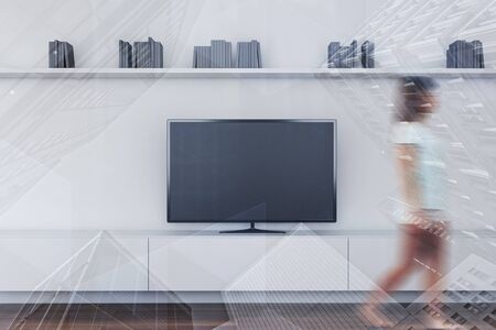 Young woman walking in modern living room interior with white walls, wooden floor and big TV set standing on white cabinet. Toned image double exposure blurred