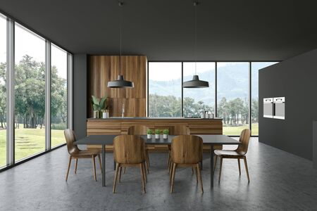 Interior of modern kitchen with grey walls, concrete floor, wooden countertop with built in cooker and sink, dining table with chairs and two ovens. 3d rendering