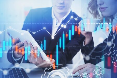 Businessman and businesswoman working with tablet at office table with double exposure of graphs. Concept of stock market and trading. Toned image