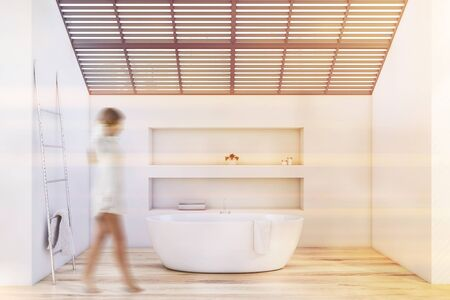 Young woman walking in attic bathroom with white walls, wooden floor, comfortable bathtub, two niches and metal ladder with towel. Toned image blurred