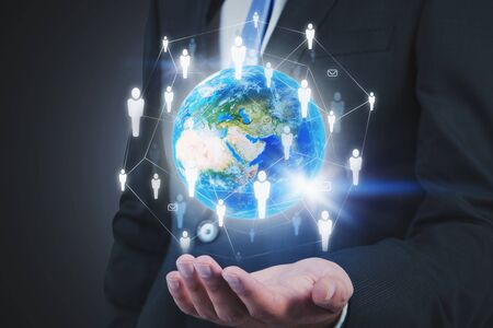 Businessman in suit holding planet hologram with social network interface. Concept of communication. Toned image double exposure.