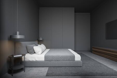 Interior of minimalistic bedroom with grey walls, concrete floor with carpet, comfortable king size bed, gray wardrobe and TV. 3d rendering