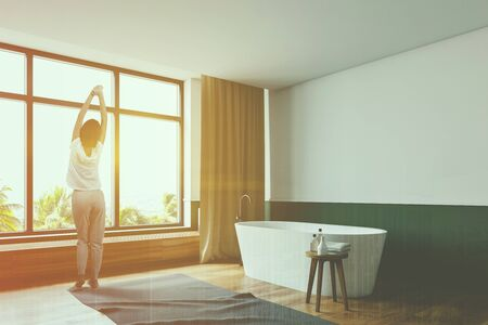 Young woman standing in modern bathroom corner with white and green walls, wooden floor with carpet and comfortable white bathtub. Toned image double exposure 写真素材 - 129623104