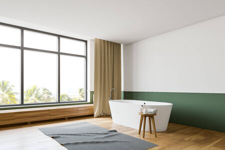 Corner of stylish bathroom with white and green walls, wooden floor and comfortable white bathtub standing under window with tropical view. 3d rendering Stok Fotoğraf