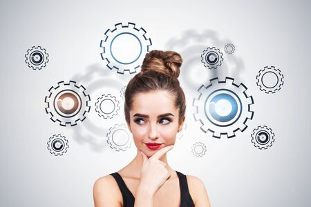 Thoughtful young woman in tank top standing near white wall with gears on it. Concept of brainstorming and strategy