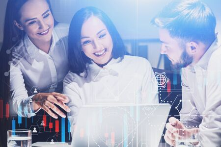 Cheerful young business people working in office with laptop and double exposure of graphs and business interface. Concept of teamwork and stock market. Toned image Фото со стока