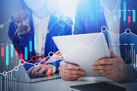 Businesswoman working with laptop near businessman with tablet with double exposure of graphs. Concept of partnership and stock market. Toned image