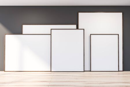Interior of empty room with gray walls and wooden floor with horizontal and vertical mock up poster frames standing on it. 3d rendering