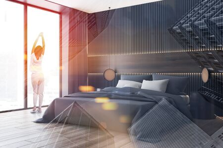 Young woman standing in modern bedroom with gray and wooden walls, king size bed with round bedside table and panoramic window. Toned image double exposure 写真素材