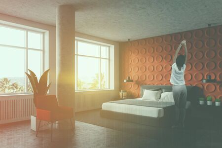 Woman standing in modern bedroom with orange and white walls, concrete floor, master bed with two bedside tables and red armchair. Toned image double exposure 写真素材