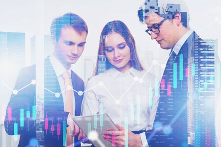 Three young business people working with tablet computer in modern city with double exposure of graphs. Concept of teamwork and stock market. Toned image Фото со стока