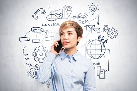 Young woman in blue shirt talking on smartphone standing near concrete wall with business plan sketch drawn on it.
