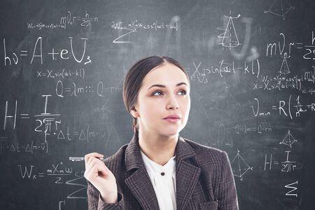 Durchdachte junge Frau mit dunklem Haar und Stift in der Nähe der Tafel mit darauf geschriebenen Formeln. Konzept der Bildung und Wissenschaft.