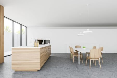 Side view of comfortable kitchen with white walls, concrete floor, wooden countertop with built in sink and cooker, dining table with chairs and two ovens. 3d rendering Reklamní fotografie