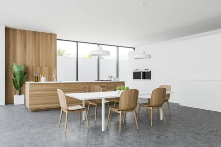 Corner of modern kitchen with white walls, concrete floor, wooden countertop with built in cooker and sink, dining table with chairs and two ovens. 3d rendering Reklamní fotografie