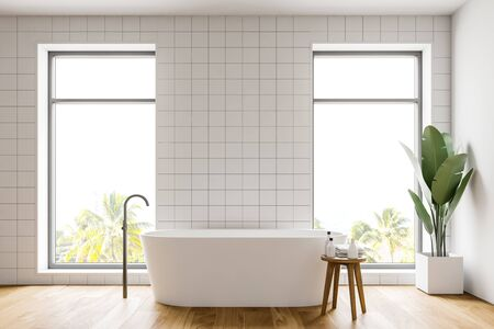 Interior of minimalistic bathroom with white tile walls, wooden floor, comfortable white bathtub and chair with towels and bottles. 3d rendering Reklamní fotografie