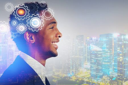 Side view of smiling young African American businessman in night city with double exposure of gears. Concept of brainstorming. Toned image