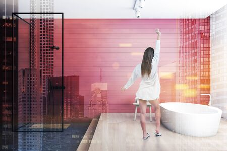 Woman in nightgown standing in stylish bathroom with red and white walls, comfortable bathtub and walk in shower. Toned image double exposure