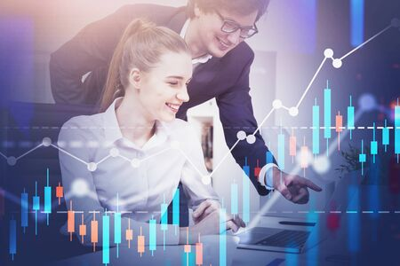 Happy young business people working with laptop in office with double exposure of forex graphs. Concept of trading and stock market. Toned image Фото со стока