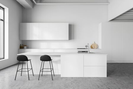 Interior of stylish kitchen with white walls, concrete floor, white countertops and cupboards and bar with stools. 3d rendering