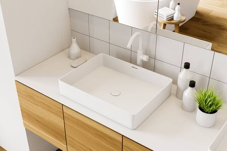 Top view of bathroom sink standing on wooden countertop in modern room with white tile walls and large mirrors. 3d rendering