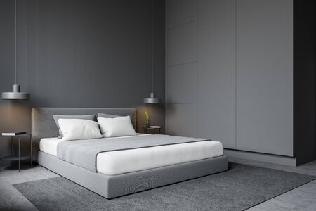 Interior of minimalistic bedroom with grey walls, concrete floor with carpet, comfortable king size bed and gray wardrobe. 3d rendering