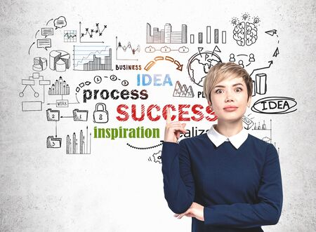 Young woman in blue dress pointing up standing near concrete wall with colorful business strategy sketch drawn on it. Concept of business planning