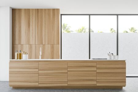 Interior of minimalistic kitchen with white walls, concrete floor, wooden countertop with built in sink and cooker and wooden cupboard. 3d rendering