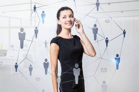 Smiling young businesswoman talking on smartphone in blurred office with double exposure of social network interface. Toned image
