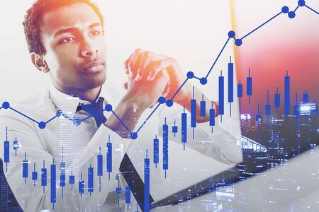 Serious young African American broker looking at laptop screen with double exposure of forex graph and night cityscape. Concept of trading and business analysis. Toned image