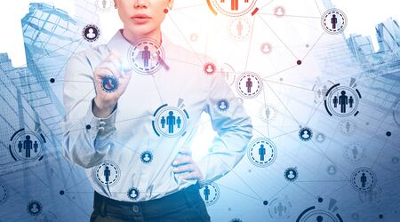 Confident young businesswoman working with futuristic HUD social network interface in modern city. Concept of HR and hi tech. Toned image double exposure