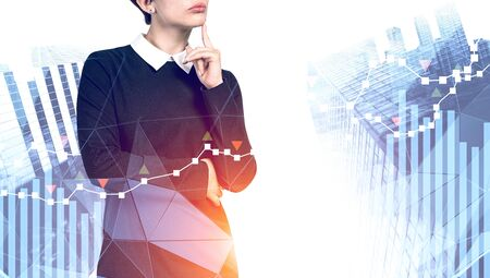 Pensive young businesswoman in black dress standing in modern city with double exposure of forex graphs. Concept of stock market analysis. Toned image Stock Photo