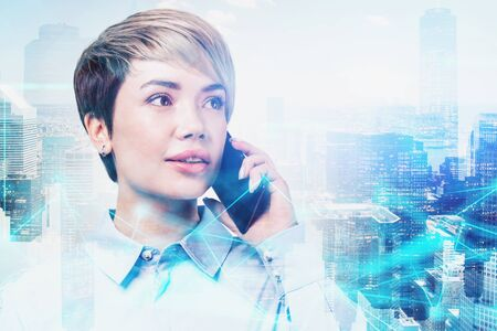 Young businesswoman with short hair talking on smartphone in modern city with double exposure of network interface. Concept of communication. Toned image
