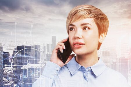 Young businesswoman talking on smartphone in modern city with double exposure of network interface. Concept of communication. Toned image