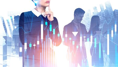 Pensive young businesswoman and her team standing together in city with double exposure of graphs. Concept of teamwork and stock market. Toned image