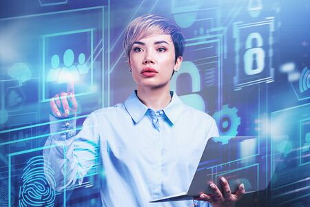 Attractive young businesswoman with short blond hair and laptop using futuristic digital business interface. Concept of hi tech and programming. Toned image double exposure